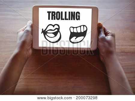 Digital composite of Trolling text and mouth cartoons on tablet in hands