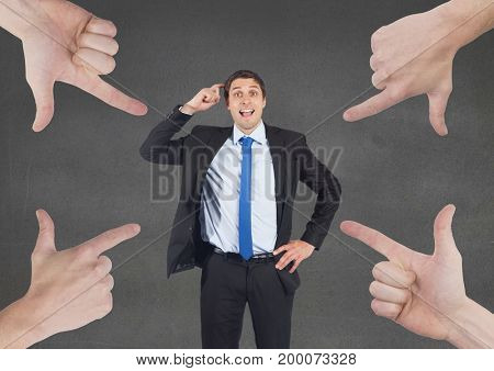 Digital composite of Hands pointing at business man against grey background