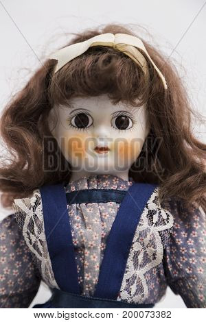 Portrait of ceramic porcelain handmade vintage doll with big eyes, wavy brown hair in old blue textile dress with embroidery, in shirt with gentle floral print , bow on white background.