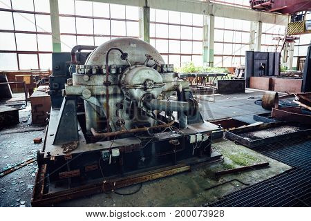 Large hall of abandoned Soviet factory with equipment, toned