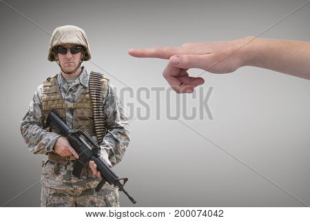Digital composite of Hand pointing at soldier against grey background