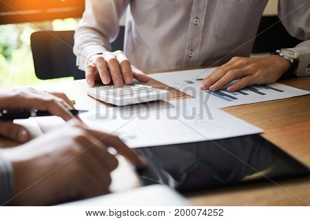 Two Young Businessmen Using Touchpad Explaining His Business Plans To His Colleagues, Organization M