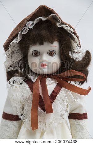 Portrait of ceramic porcelain handmade vintage doll with brown hair in old textile dress with gentle embroidery with brown lines, in hat and linen bow on white background.