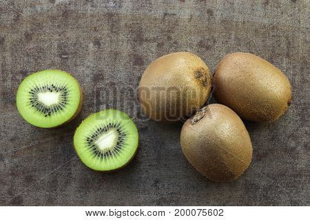 fresh kiwi fruits and a cut one on a grungy metal background
