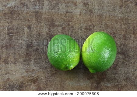 two lime fruits on a grungy metal background