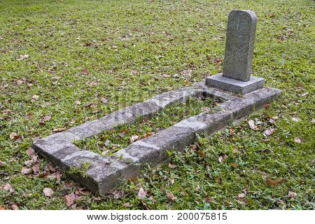 Solitary grave on field with green grass