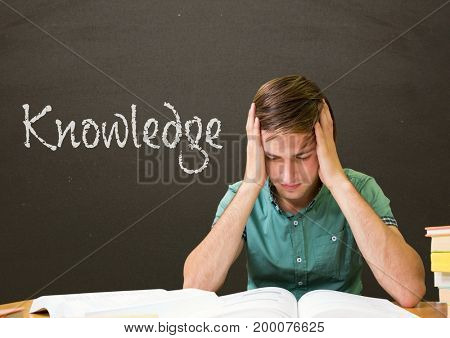 Digital composite of Worried student boy at table against grey blackboard with knowledge text