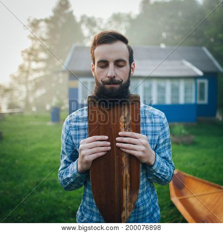 handsome man with closed eyes holding wooden canoe paddle while standing in courtyard
