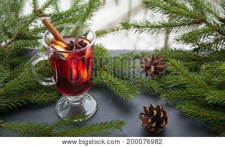 Hot mulled wine with cinnamon and christmas tree on black slate dish.