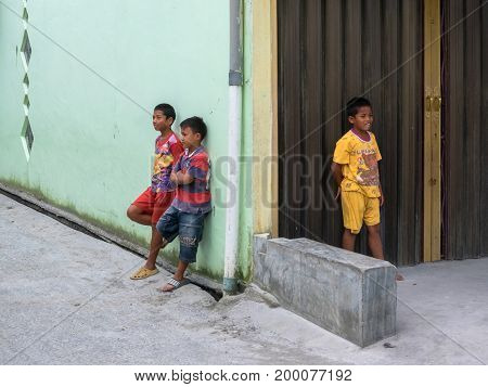 BERASTAGI INDONESIA 15 MAY 2017 : Three indonesian children near the wall on the street at countryside area of Berastagi city Northern Sumatra.