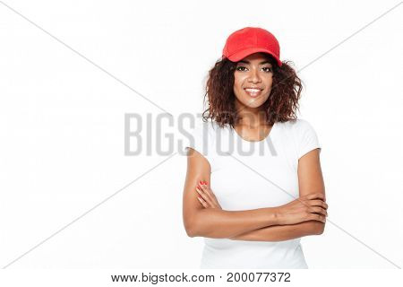 Picture of happy young african lady standing isolated over white background. Looking at camera wearing cap.