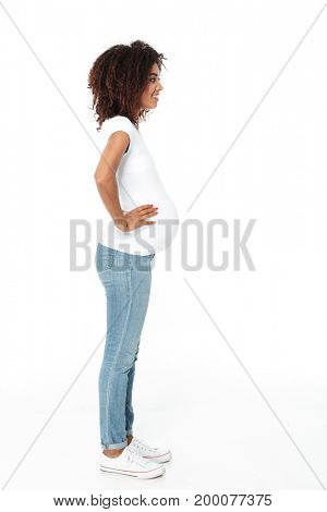 Picture of happy young pregnant african woman standing isolated over white background. Looking aside.