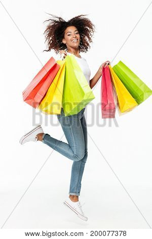 Picture of smiling young african woman jumping isolated over white background. Looking camera holding shopping bags.
