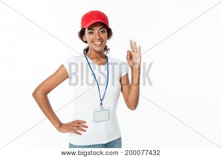 Photo of cheerful young african lady standing isolated over white background. Looking at camera wearing cap showing okay gesture.