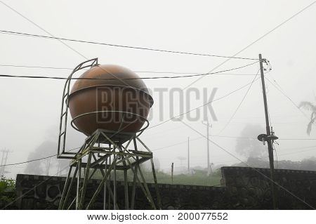 Orange water tower and wires in foggy gloomy atmosphere with low visibility conditions