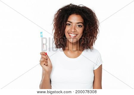 Image of cheerful young african lady standing isolated over white background. Looking at camera holding toothbrush.