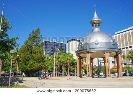 People walking through Joe Chillura Courthouse Square, metallic dome, Tampa, Florida, United States, April 28, 2017