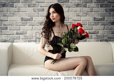 beautiful brunette woman in lingerie and with roses in hands sitting on couch