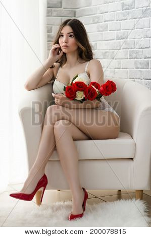 luxurious beautiful woman with bouquet of flowers in lingerie