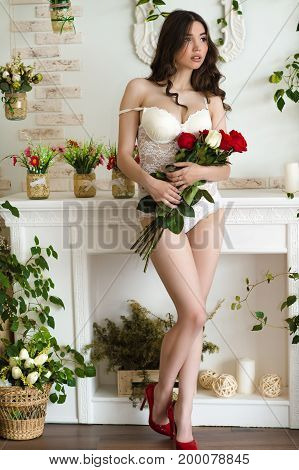 charming woman in lingerie with bouquet roses stands in full length
