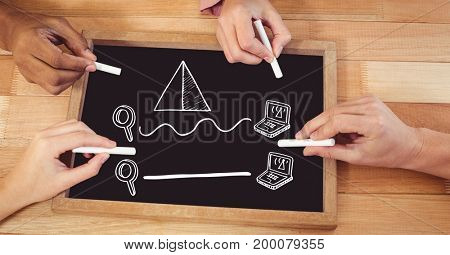 Digital composite of Hands drawing computer diagrams on blackboard