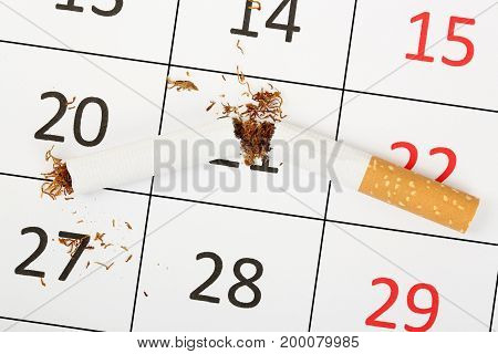 broken cigarette on calendar quit smoking concept