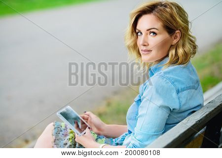 Happy middle aged woman relaxing on a bench in the park on a summer day. Mood of summer and carefree vacations. Beauty, cosmetics.