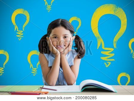 Digital composite of Schoolgirl at desk with light bulb graphics