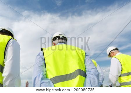 Men Are Wearing Yellow Waistcoats And Protective Helmets