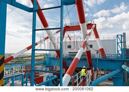 A Red-white Loading Crane Near The Sea