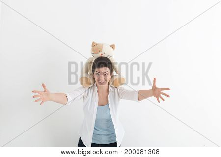 Success positive emotions. Happy young woman in white shirt stretching hands ahead wanting to hug someone. Plush cat sits on her neck.