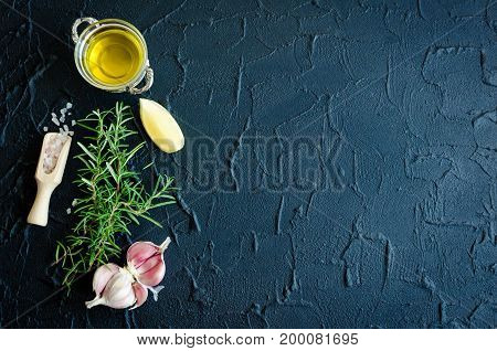 Rosemary garlic lemon salt and olive oil on dark stone table. Herbs and spices concept. Cooking ingredients. Food flat lay. Creative layout with place for text. Copy space. Top view.