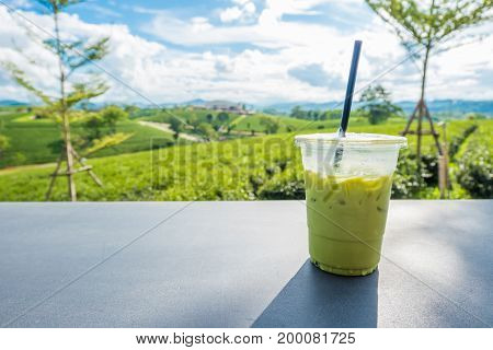 Matcha Iced Green Tea In Clear Plastic Glass On Table With Tea Plantation Background At Choui Fong C