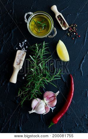 Herbs and spices selection - rosemary garlic lemon salt chili pepper peppercorns and olive oil on dark stone table. Cooking ingredients concept. Food flat lay. Top view.