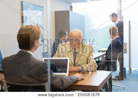 Young financial advisor sitting in front of laptop, consulting senior client with his investment strategy. Business people on business meetings.