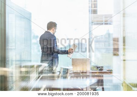 Businessman talking on a mobile phone while looking through modern corporate office window, holding financial newspaper. Reflections of building interior in window glass.