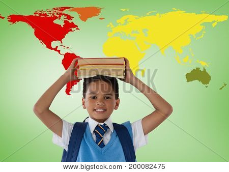 Digital composite of Schoolboy holding books on head in front of colorful world map