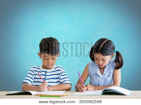 Digital composite of School kids writing at desk in front of blue background
