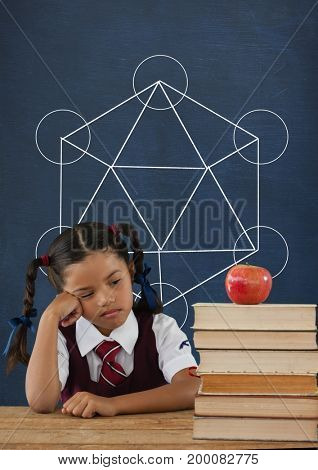 Digital composite of Sad student girl at table against blue blackboard with school and education graphic