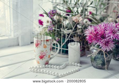 Beautiful pink bouquet of flowers asters in glass vase with cup of coffee or tea on white table near the window. Cozy autumn or winter breakfast. Provence style. Lifestyle morning background.