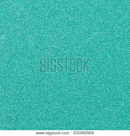 A digitally created turquoise green glitter paper background texture.