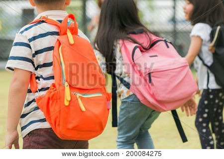 Three pupils of primary school go hand in hand. Boy and girl with school bags behind the back. Beginning of school lessons. Warm day of fall. Back to school. Little first graders.