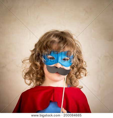 Super hero kid with fake hipster mustache