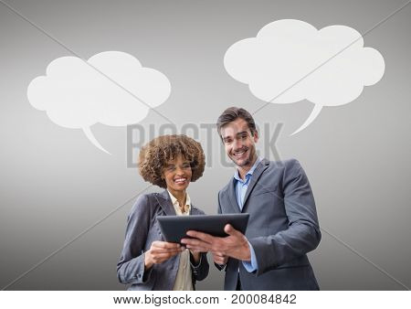 Digital composite of Business people with speech bubbles looking at a tablet against grey background