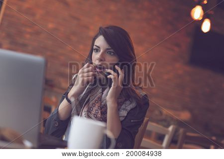 Attractive young brunette sitting in a cafe and having a phone conversation