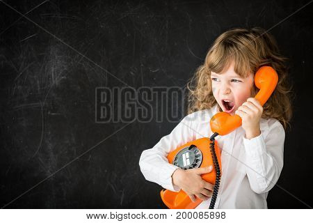 Angry child shouting by vintage phone against blackboard