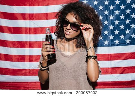 Image of serious african young lady wearing sunglasses standing over USA flag drinking aerated water. Looking aside.
