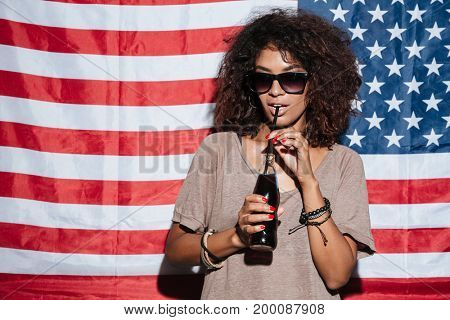 Picture of serious african young lady wearing sunglasses standing over USA flag drinking aerated water. Looking aside.