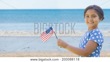 Digital composite of Happy girl holding a USA flag in the beach