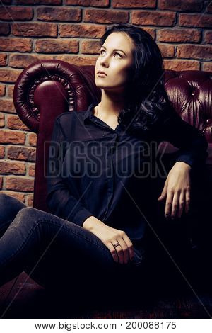 Beautiful dreamy girl sitting on a floor by a sofa. Beauty, fashion. Natural make-up, cosmetics.